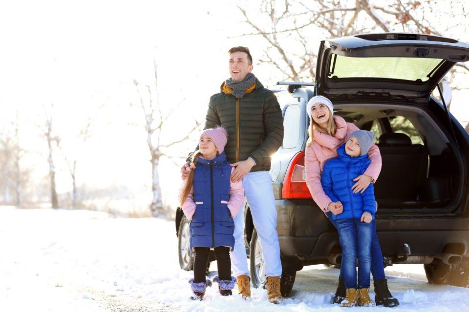 family near snowy car