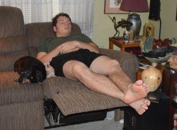 man sleeping beside dog