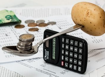 coins on spoon with potato and calculator