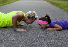 mother and daughter exercising on road