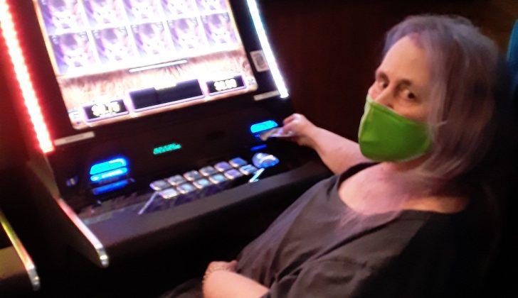 old woman using slot machine